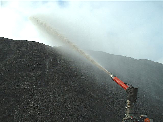 water is being sprayed from a water cannon toward the top of a barren cliff. It shows the strong force of the water & the ability to target the water accurately.